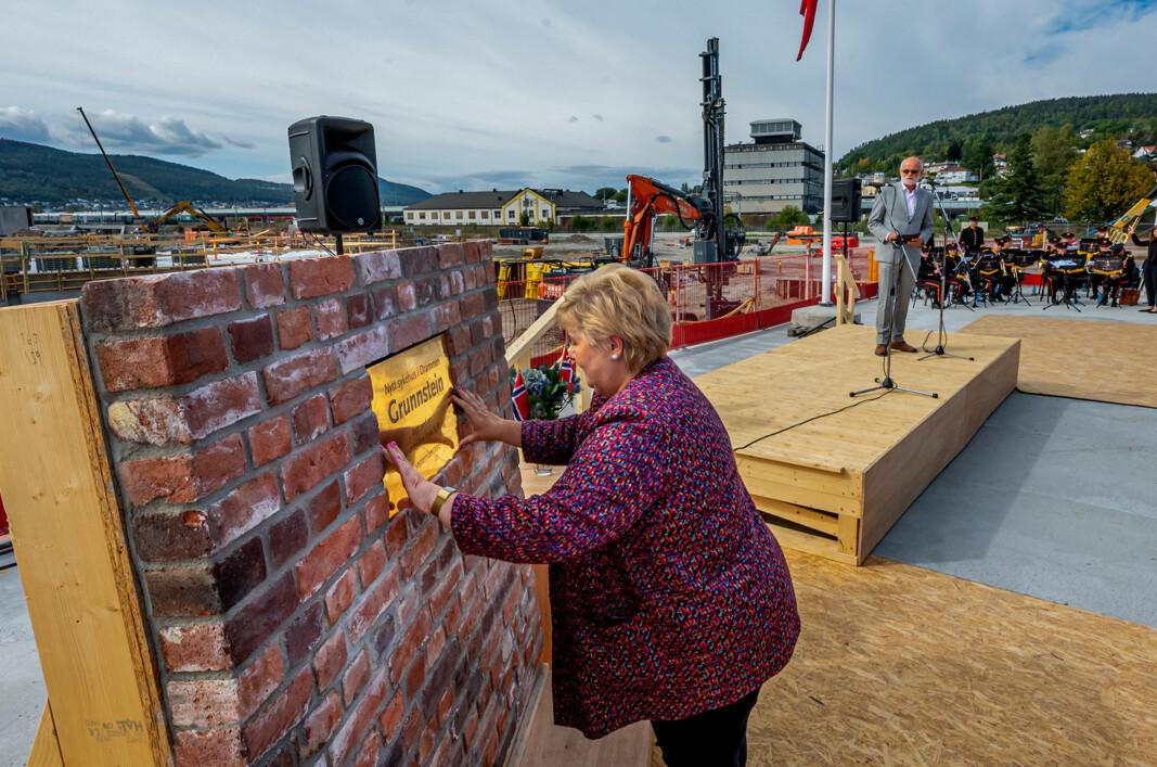 GRUNNSTEIN: Statsminister Erna Solberg plasserer grunnsteien til sykehuset i en teglsteinsmur fra det gamle industriområdet. I bakgrunnen Arnstein Hodne som har hovedansvar og daglig tilsyn med prosjektet.