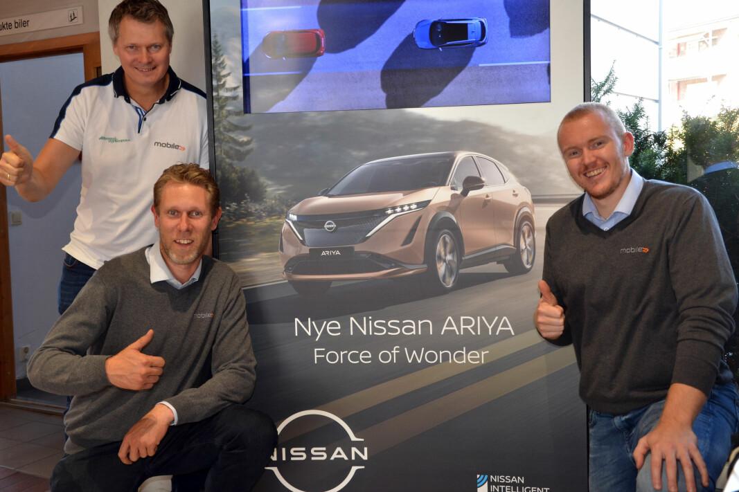 SELGES UPRØVD: Tom Erik Moen (stående), Marius Sørum (t.v.) og selger Eirik Hunsrød Skau kan foreløpig bare vise frem en plakat av Nissan Ariya, og gleder seg stort til de kan vise frem bilen live i butikken!