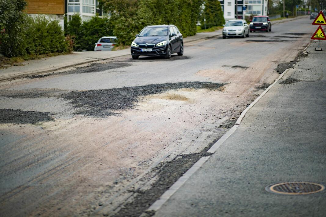 AUSTADVEIEN: Grus, dype hull, skarpe asfaltkanter og manuell dirigering preger veistrekningen for tusenvis av bilister, busser, og myke trafikanter.